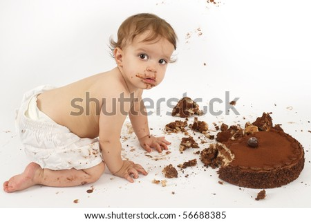 An adorable one year old girl enjoying her first birthday cake. - stock photo