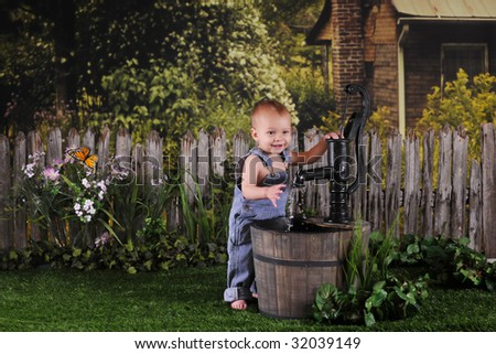 An adorable one-year-old happily playing with an old water pump by an old farm house. - stock photo