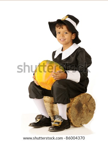 An adorable preschool-aged Pilgrim boy holding a pumpkin while sitting on an old log.  On a white background. - stock photo
