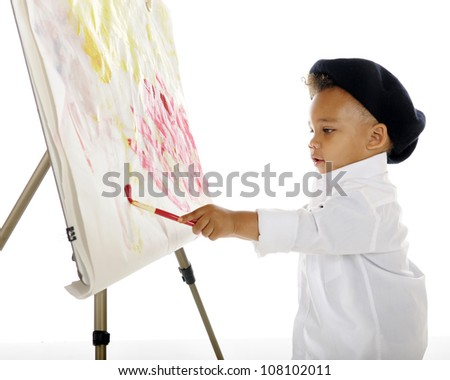 An adorable preschool artist painting on an easel while wearing a white smock and black French beret.  On a white background. - stock photo