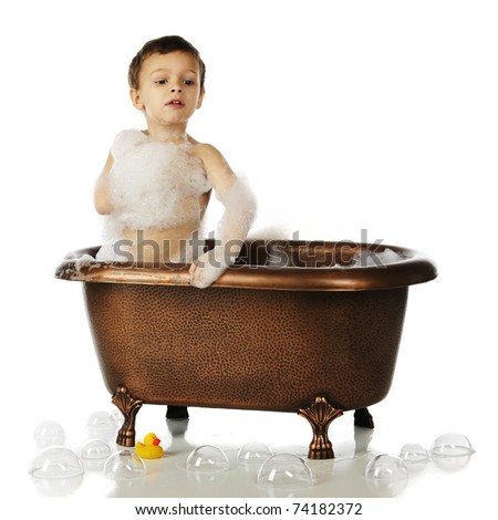 An adorable preschool boy all suds-up in a copper tub.  He's on his knees looking for his big rubber duck.  Isolated on white. - stock photo