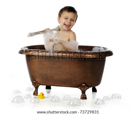 An adorable preschool boy happily scrubbing himself in a copper, claw-foot tub.  Isolated on white. - stock photo