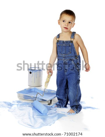 An adorable preschool boy in overalls, giving a quizzical look as he uses a roller full of blue paint on the floor.  Isolated on white. - stock photo