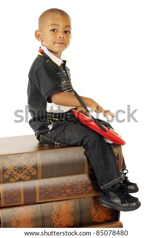 An adorable preschool boy playing a toy electric guitar on a stack of huge books. - stock photo