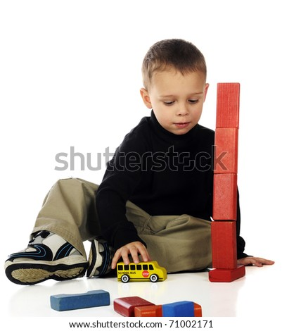 An adorable preschool boy playing with blocks and a toy school bus.  His block tower is about to tumble.  Isolated on white. - stock photo