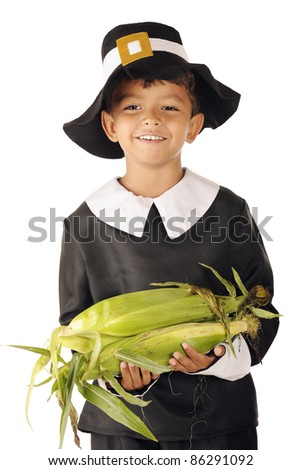 An adorable preschool boy wearing Pilgrim clothes carrying an armload of fresh corn on the cob. - stock photo