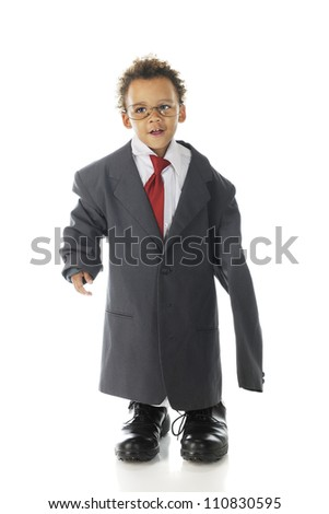 "An adorable preschool ""businessman"" dressed in an over-sized dress shirt and suit coat with glasses and a tie and his dad's shoes.  On a white background."