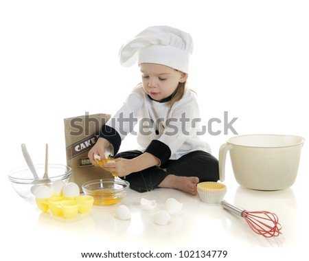 "An adorable preschool ""chef"" cracking eggs as she makes her first cake.  On a white background. - stock photo"