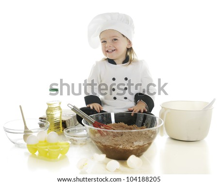 "An adorable preschool ""chef"" happily making her first cake.  On a white background. - stock photo"