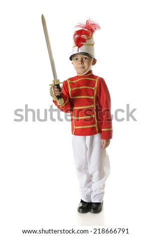 """An adorable preschool """"Christmas soldier"""" standing straight and tall in his red, white and gold uniform and holding his sword blade high.  On a white background. - stock photo"""