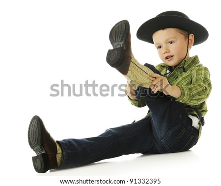 An adorable preschool cowboy putting on his boots.  On a white background. - stock photo