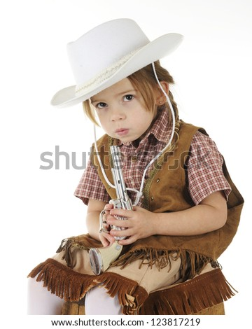 An adorable preschool cowgirl blowing on the end of her toy gun.  On a white background. - stock photo