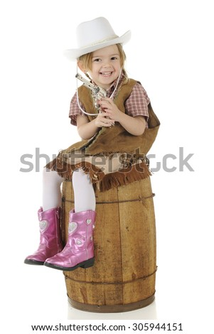 An adorable preschool cowgirl happily holding her gun while sitting on a rustic wood barrel.  On a white background. - stock photo