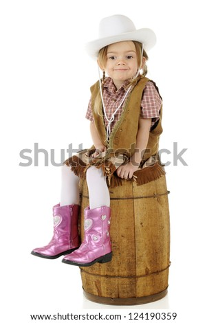 An adorable preschool cowgirl sitting on a rustic wood barrel looking smug.  On a white background. - stock photo