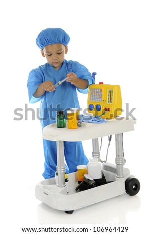 "An adorable preschool ""doctor"" in blue scrubs preparing meds at his emergency cart.  On a white background."