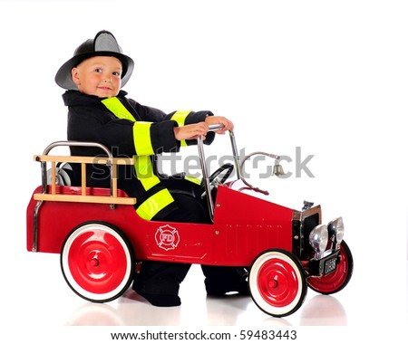 An adorable preschool fireman dressed and ready for a fire in his truck.  Isolated on white. - stock photo