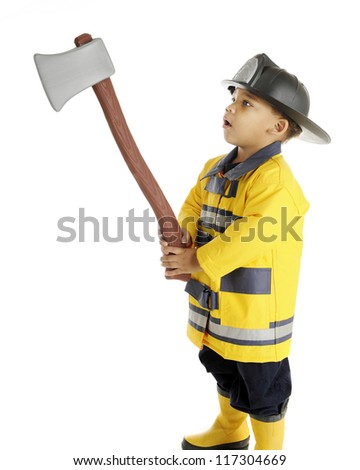 An adorable preschool fireman examining his raised hatchet.  On a white background. - stock photo