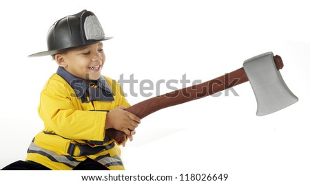 An adorable preschool fireman happily wielding a hatchet.  On a white background. - stock photo
