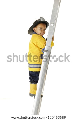 An adorable preschool fireman looking back at the viewer as he carefully climbs a long ladder.  On a white background.