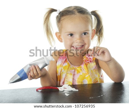 An adorable preschool girl happily loading her own toothbrush with toothpaste.  On a white background. - stock photo