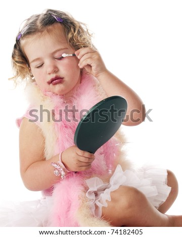An adorable preschool girl in boas and a petticoat applying eye makeup by herself. - stock photo