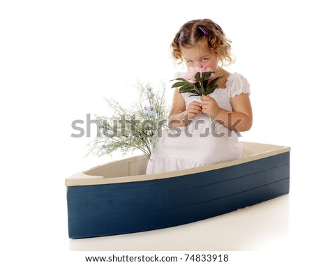 An adorable preschool girl smelling a large pink flower while sitting in a small blue boat. - stock photo