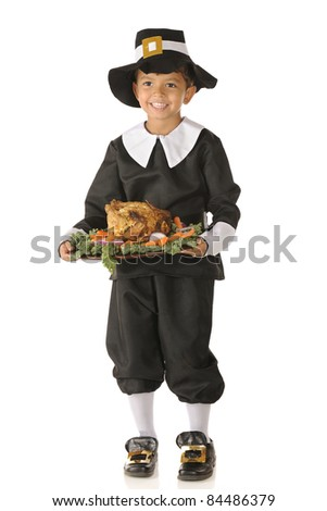 """An adorable preschool """"pilgrim"""" with a wooden plate full of Thanksgiving food.  Isolated on white. - stock photo"""