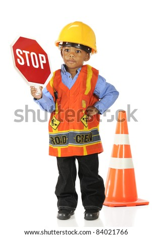 """An adorable preschool """"road crewman"""" in a hardhat and safety vest, holding up a stop sign.  Isolated on white. - stock photo"""