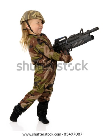 """An adorable preschool """"soldier"""" delightedly shooting her toy machine gun.  Isolated. - stock photo"""
