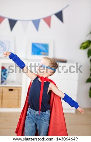 An adorable preschool superhero, hands forward, cape blowing as he flies through space to perform a rescue - stock photo