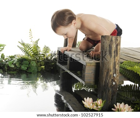 "An adorable preschool ""swimmer"" looking down into the water from a rustic, old dock.  On a white background."