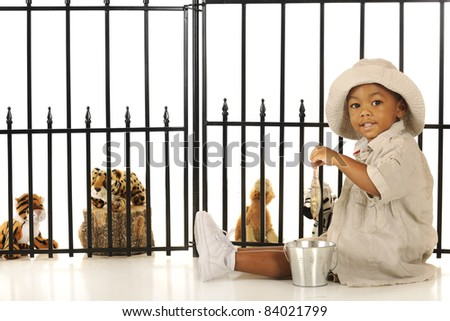 An adorable preschool zookeeper feeding fish to the critters in his pretend zoo. - stock photo