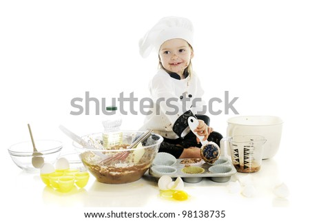 "An adorable preschooler ""chef"" happily making her first chocolate cake.  On a white background. - stock photo"