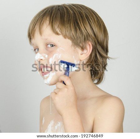 An adorable preschooler concentrating as he attemtps to shave like his dad. On a white background. - stock photo