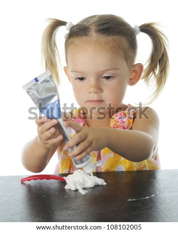 An adorable preschooler concentrating on squeezing toothpaste onto her tooth brush.  Focus on child's eyes.  On a white background. - stock photo