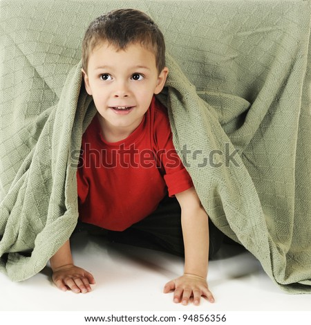 """An adorable preschooler crawling out from under a blanket-covered table, his """"playhouse."""" - stock photo"""