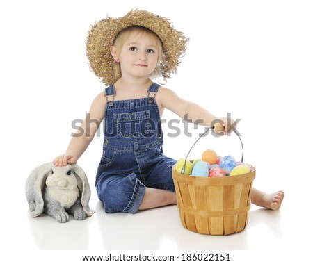 An adorable preschooler happily holding her fruit basket of colored eggs while petting a bunny.  On a white background. - stock photo