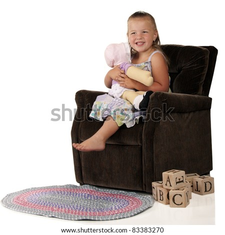 An adorable preschooler hugging her doll while sitting in a child-sized plush chair.  A braided rug and pile of alphabet blocks are on the floor nearby. - stock photo