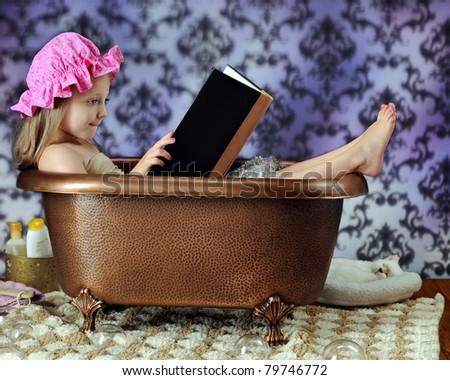 An adorable preschooler in a bathing hat reading a book in a copper bathtub. - stock photo