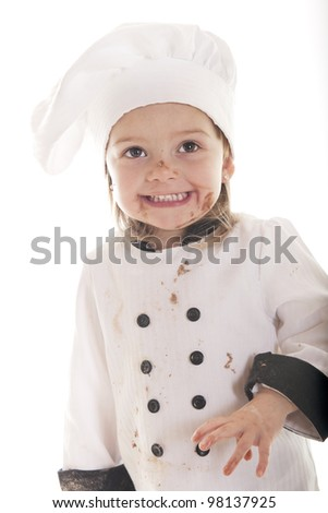 An adorable preschooler in a chef's outfit, happily messy from her chocolate cake batter.  On a white background. - stock photo