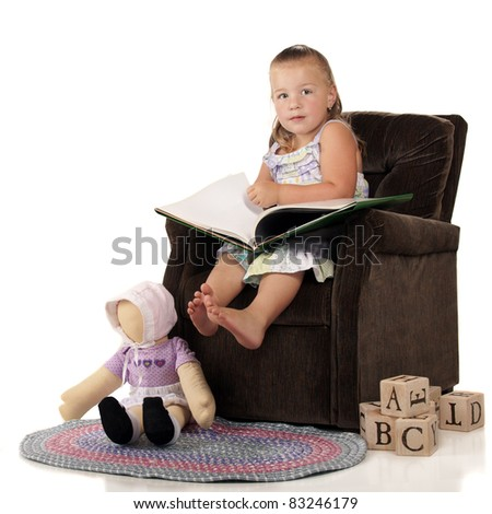 An adorable preschooler in a child-sized stuffed chair with toys nearby.  She's looking up from a big book to the viewer. - stock photo