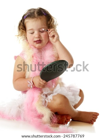 An adorable preschooler in a petticoat and pink boas applying her mommy's makeup on herself.   - stock photo