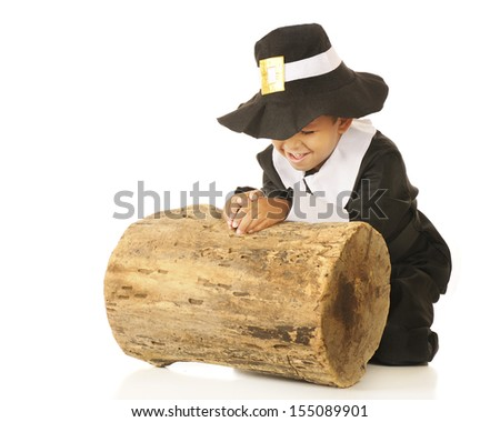 An adorable preschooler in a pilgrim outfit praying, giving thanks, by an old log. - stock photo