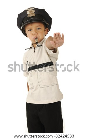 An adorable preschooler in a policeman's hat blowing his whistle and holding out his hand demanding traffic to stop.  Isolated. - stock photo