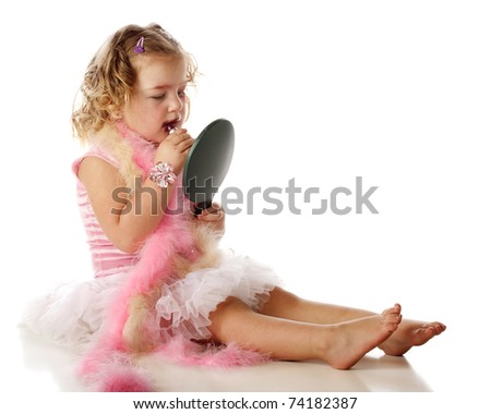An adorable preschooler in boas and a petticoat, applying her mommy's makeup onto herself. - stock photo