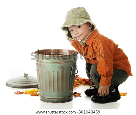 An adorable preschooler in fall colors squatting beside a small trash can as he cleans up fallen autumn leaves.  On a white background. - stock photo