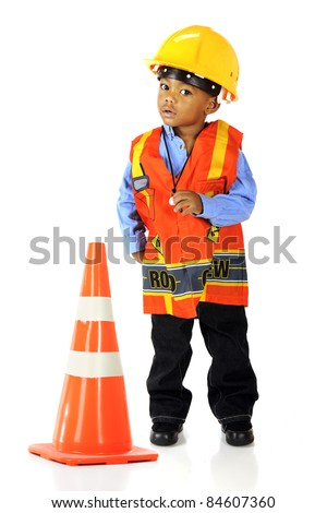 An adorable preschooler in road crewman safety gear by a an orange traffic cone.  Isolated on white. - stock photo