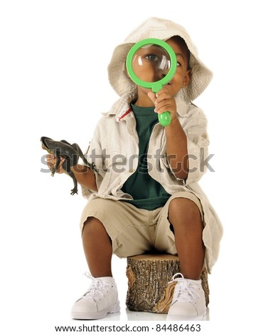 An adorable preschooler looking at the viewer through a magnifying glass.  He's dressed in beige safari clothes and holds a frog in his other hand. - stock photo