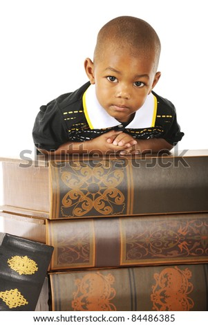 An adorable preschooler looking at the viewer while leaning over a stack of very large books. - stock photo