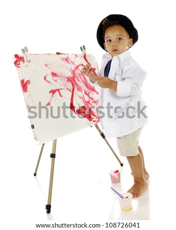 An adorable preschooler looking back at the viewer as he creates his own painted masterpiece.  He has a slightly splattered face and wears a smock and beret.  On a white background. - stock photo